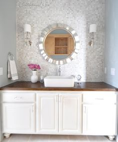 Repainted cabinet with feet added to give height.  Glass tiled wall, long arm sconces, vessel sink, mirror.  http://www.centsationalgirl.com/2013/02/the-lucky-backsplash/