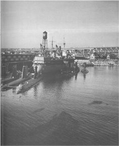 USS Fulton AS-11 at the Connecticut State Pier,New London,CT,with from left/right~USS Nautilus SSN571,USS Halfbeak SS-352,  USS Bang SS-385,  USS Tusk SS-426 immediately astern. Moored to Fulton's starboard side are three additional unidentified submarines. Photo from Subron 10 Cruise Book for 1964-1965.