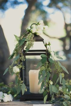 Greenery covering candle in lantern  #centerpiece #wedding #flowers #decor