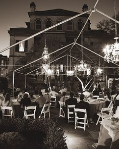 Vintage French chandeliers hang from a tent frame