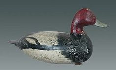 Realized Price:  $60,000 Singular rig mate pair of redheads c1920's by Ira Hudson (1876-1949) of Chincoteague, VA. Both heads strongly turned, drake to the left and hen to the right. Especially attractive, plump football shape and thin flat paddle tail so characteristic of Hudson's best work. Strong original paint with well-defined swirling at edge of both breasts. Surface is crackled on breast and on rump of both. Thin, tight check in back and thin crack on bot-tom of both. Each h thin flat, shorebird decoy, antiqu decoy