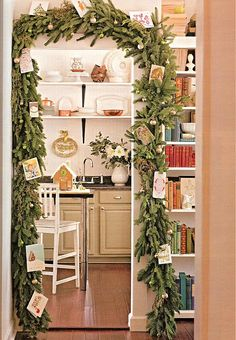 Attach greens around living room arch using command hooks.