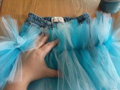 DIY Denim tutu. Upcycle an old pair of jeans that may be too short but still fit in the waist. Cut off in a straight line just above crotch area. Lay down tulle flat over the now denim skirt and sew one straight line down the middle. For layers just lay tulle so that more of the length is below where you sew. That's it! Fluff out the tulle and you're done.