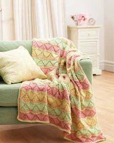 A triangle lace pattern follows the multicolored stripes in this beautiful blanket. Make one to match your decor in Bernat Super Value.