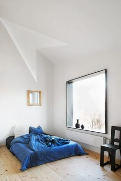 Blue bed on floor in bright clean room.