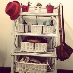 Biblioteca de palo pintada con canastos de mimbre y latas de colores para guardado de objetos.