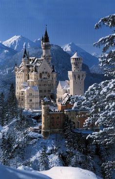Neuschwanstein Castle, Germany...perched on a craggy hillside and surrounded by a backdrop of spectacular snow-covered mountain peaks.
