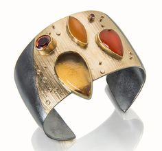 Corona cuff in the colors of the blazing sun.   Citrine, carnelian, faceted orange tourmaline, set in 22k gold and oxidized silver.  http://sydneylynch.com/onekind.html