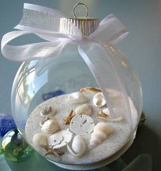Fill a clear ornament with sand and shells, love it!  Would be cute to put sand  and in from beaches we visit, then label with a tag that gives date and name of beach visited