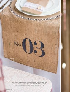 Instead of table numbers, have it printed on burlap table runners.
