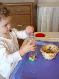 Pom-poms into a water bottle - Easy fine motor control activity for toddlers. #weteach