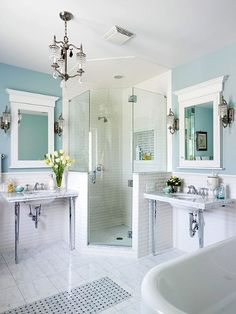 Bathroom with corner shower, white tile, blue walls.