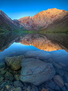 The Eastern Sierra mountains reflected in a still cold lake. Landscape photography by Kevin McNeal.
