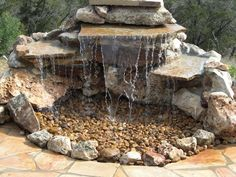 Stunning Relaxing Garden And Backyard Waterfalls: Small Man Made Water Fall Design With Flat Stones Stacked Together To Create Illusion Of A Small Cliff Where The Water Falls Into A Bed Of Pebbles ~ aureasf.com Decorating Inspiration