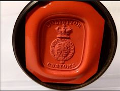#2 antique red wax seal which is easy read.. SOLICITOR CUSTOMS with the Royal Coat of Arms in the Garter with the Victorian Crown above....the seal is a little cracked... the paper lable under the lid ... HALFHIDE & SONS Seal Engravers to Her Majesty Coventry Street London..... It comes in a circular LIGNUM VITAE box.