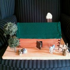 Homemade log cabin craft:  glue rolled up construction paper to a shoe box, bend lid to make roof and cover with felt.  Door and chimney made with Popsicle sticks.  Trees & fence made with sticks from yard.  Added rocks and tied horse to fence for finishing touch!