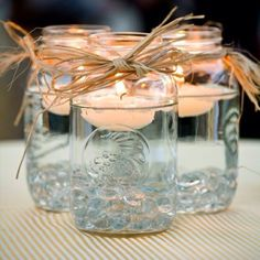 Simple, cheap & cute for an outdoors rehearsal dinner or reception - mason jars with jute bows and floating candles