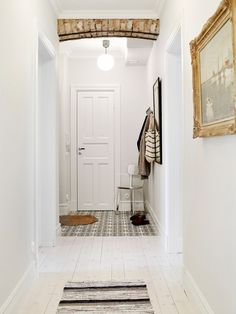 Neutral toned entryway with exposed brick and white hardwood floors.