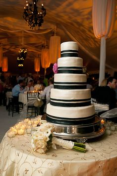 a white five tier round wedding cake with black borders on a silver cakestand sitting on a table covered with a gold tablecloth, ivory candles, and the brides ivory bouquet - photo by Houston based wedding photographer Adam Nyholt