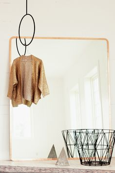 DIY copper taped mirror. I like that wire basket.