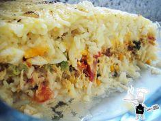Arroz temperado.  Em uma panela, refogue ½ cebola e 2 dentes de alho, misture com frango desfiado ensopado.  Em um refratário coloque uma camada (1 xícara) de arroz cozido e misturado com uma lata de milho, e acrescente aí: frango, 1 tomate picado, brócolis, 3 ovos cozidos e fatiados e bastante queijo mussarela, jogue por cima 1 xícara de arroz cozido, cubra com mais queijo mussarela, polvilhe orégano e leve para o forno por uns 20 a 30 minutos ou até gratinar o queijo em cima.