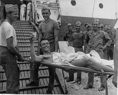 USS Solace, Iwo Jima Operation. A wounded Marine (injured 3 days  previously) takes pineapple juice along as he is carried down the  gangway by Marine stretcher bearers at Guam. World War 2