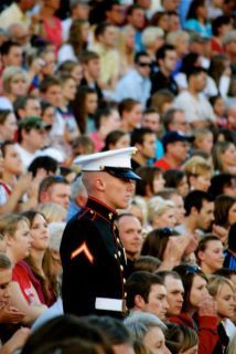Standing at attention for the National Anthem.  Only a Marine.