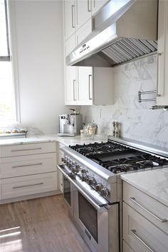 Sleek hardware + white cabinets + whitewashed wood floor + marble