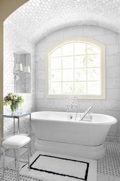 Clean white bathroom.  Floor to ceiling tile + free standing tub + basket-weave