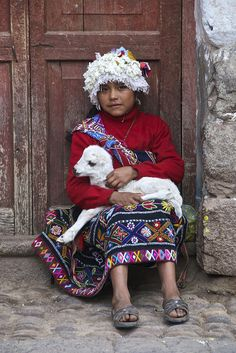 Quechua girl sitting on a doorstep with a young Llama on her lap, in Pisac, Peru.