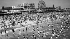 "A bird's eye view of tourists on the beach in <a href=""  http://www.travelchannel.com/video/coney-island-boardwalk""> Coney Island, NY</a>."