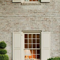"""""""The red brick was hard and lifeless before.. A limewash (paint diluted with water and mixed with sand) softened up the harsh brick. They continued to fine-tune the facade by painting all the shutters and trim Pratt & Lambert's Lambswool. This new creamy color scheme makes the home's original Buckingham gray slate roof stand out. So. Living"""