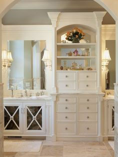 Love the built-in cabinets, doors and detail, arches, travertine floors