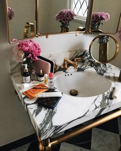 Aimee Song - Tip: Considering a remodel? Brushed gold or bronze hardware against black and white marble is an unexpectedly cool approach to the powder room.
