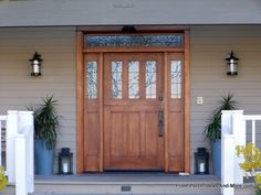 All this exquisite wooden front door needs are some simple symmetrical decor: lights, pots, and lanterns. Front-Porch-Ideas-and-More.com #porch