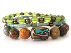 Bohemian beaded stretch bracelets featuring 10mm red creek jasper beads, a handcrafted Tibetan focal bead with brass (inlaid with turquoise and coral chips), turquoise jasper beads, chartreuse frosted glass beads and antiqued brass accent beads. Gorgeous! Rock & Hardware Jewelry