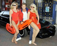 David 'The Hoff' Hasselhoff poses at a photocall with two swimsuit-clad Baywatch models in London, England before performing in concert at Leicester Square Theatre