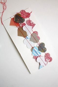 For invitations, a top fold over with these mini hearts--or bunting or tinsel or whatever you're decorating your reception with--stitched across a rectangle of vellum and glued down