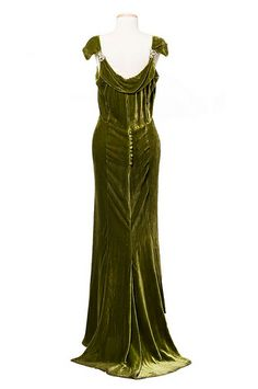 Olive green silk velvet dress, 1930s. The dress has a boat neckline, rhinestone shoulder clips and a short train in back. It was worn by Miss Fanny Eliza Hume (1882-1950) of Charleston and bears a McAvoy/Chicago label. Charleston Museum.
