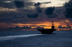 The aircraft carrier USS George Washington (CVN 73) is underway near Guam at sunset.