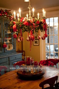 A Christmas wreath gorgeous ribbon and fun ornaments make this simple chandelier the focal point in this room.  www.showmedecorating.com