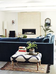 Living Room - A bone-color brick veneer fireplace set behind a blue velvet sofa and printed ottoman