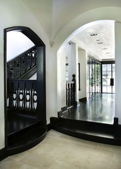 Incredible historic home with arched vaulted ceiling and black hardwood floors. The stairway features black Art Noveau style railings which contrast the white walls. Leading down the hall from a tiled foyer a light filled room is wrapped in black metal French doors.