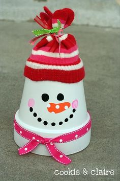 Paint a terra cotta clay pot white, add a bit of face paint fun and then top with a 'tied glove' stocking hat from the $1 store add a bit of beribboned whimsy for the scarf.