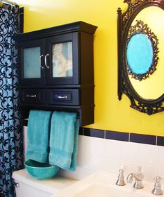 Love everything in this picture- teal towels, yellow walls, that mirror!
