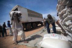 11 February 2014. Shangil Tobaya: Community members in Nifasha camp for Internally Displaced Persons (IDP), North Darfur, unload bags of sorghum from a World Food Programme (WFP) truck. Photo by Albert Gonzalez Farran, UNAMID - www.albertgonzalez.net