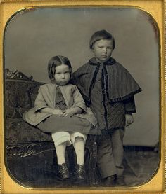 There is a posting stand behind the child in the dark cape who is standing. The seated child seems terribly unhappy with having to take this picture, too.