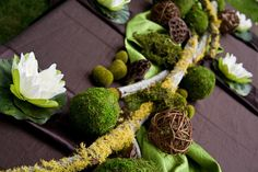 Layers of textured linens in chocolate and moss green with tree limbs, moss, and pods arranged down the center of the table helped create to bayou atmosphere.  A lily pad was placed at each setting on top of satin chocolate brown napkins.  |  real parties « Belleza e Luce