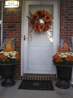 use metal stakes to secure pumpkins in planter with flowers.