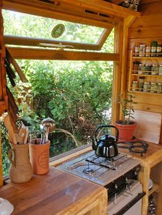 Kitchen in tiny home.....Like the big window behind the stove.   TINY HOMES are a great way to conserve energy (especially for heating and cooling), and conserve resources.   It's tiny = less resources to build.